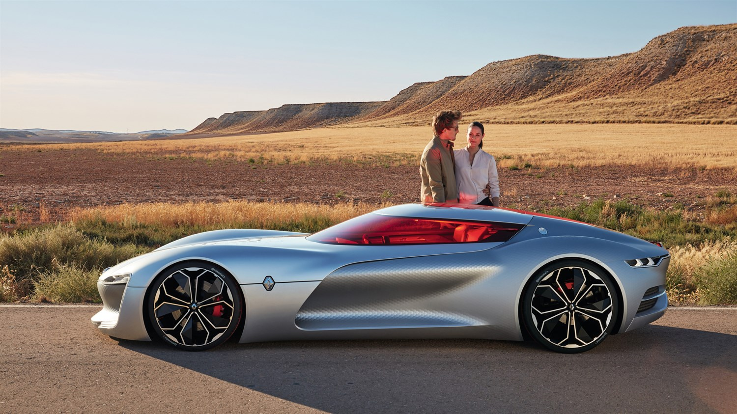 A couple sitting inside Renault TREZOR concept car with the sliding roof door open
