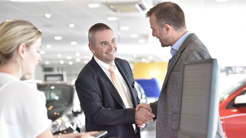 A customer shakes hand with Renault salesman